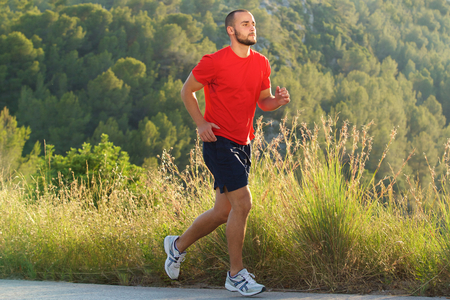 man side view: Full body portrait of a fit man running outdoors Stock Photo