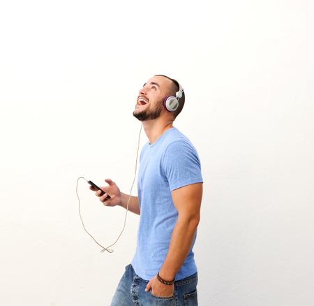 audifonos: Chico feliz que recorre con el teléfono celular y los auriculares contra el fondo blanco