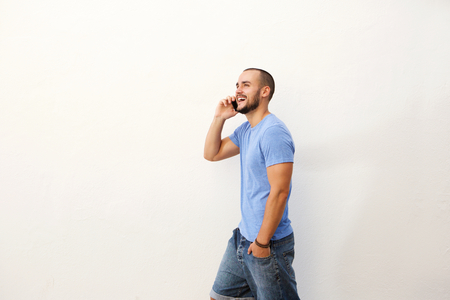 profile: Cool young man with beard walking and talking with mobile phone