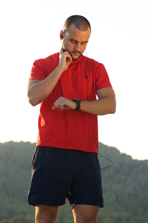 PULSE: Young man keeping in shape and checking pulse with watch