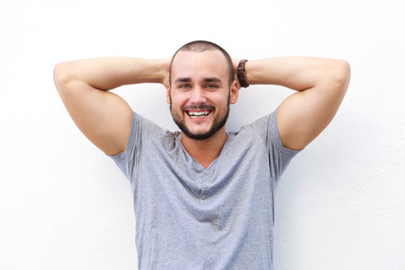 hands on head: Close up portrait of handsome young man smiling with hands behind head