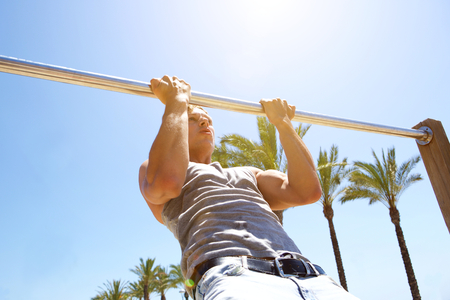 pull up: Healthy young man pull up exercise workout outdoors