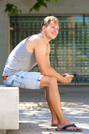 young guy: Side portrait of a happy young man sitting outside with mobile phone