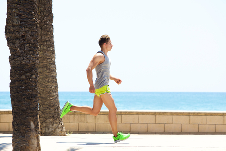 green man: Young fitness man running by the sea side