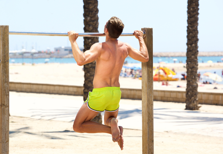 pull up: Muscular man physical training pull up workout exercise at the beach Archivio Fotografico