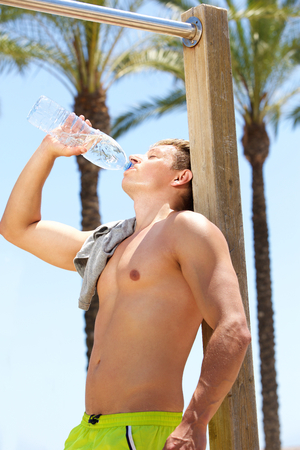 thirst: Young fitness guy drinking water after workout Stock Photo