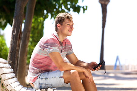 Side portrait of a smiling young man sitting outside with mobile phone