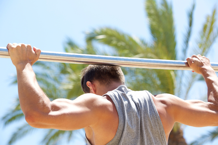 grabbing at the back: Strong man exercising on pull up bar outside