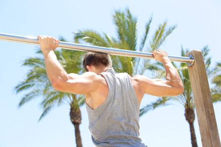 grabbing back: Man holding on to pull up bar during fitness exercise workout