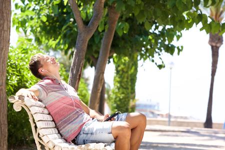 Zijportret van een gelukkige jonge mens die van muziek van mobiele telefoon geniet Stockfoto