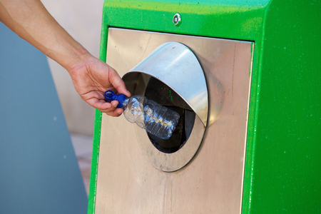 throw away: Close up male hand throwing away plastic bottle in recycling bin