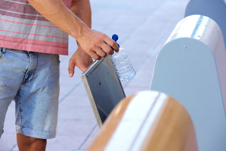 Close up man hand putting plastic bottle in recycling bin Banco de Imagens