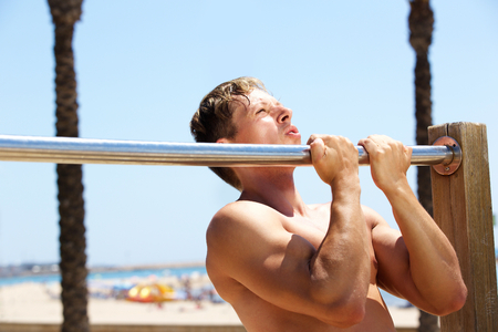 pull up: Fitness guy pull up workout routine by the beach Stock Photo
