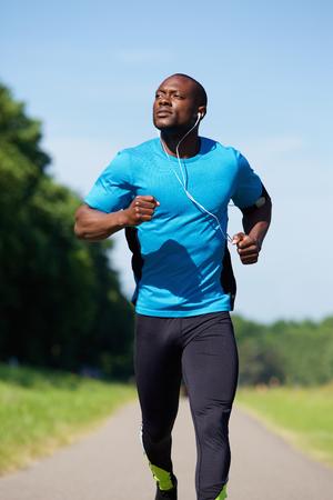 fitness hombres: deportivo hombre afroamericano joven que se ejecuta fuera Foto de archivo