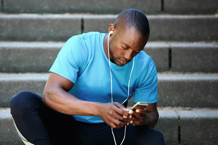 young guy: Handsome african american man listening to music and looking at mobile phone