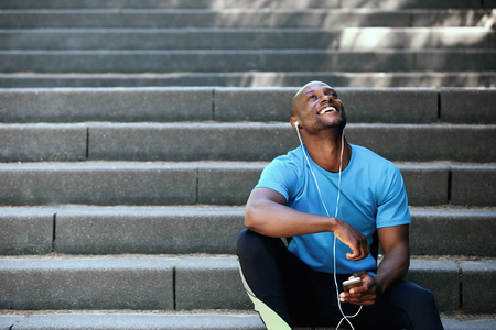 black: Portrait of a happy african american man laughing with mobile phone and earphones
