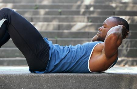 胃クランチを行うフィット アフリカ系アメリカ人の側面の肖像画 写真素材