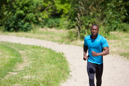 modern lifestyle: Active african american man running on path outdoors