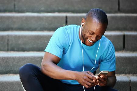 Portrait eines lächelnden Mann, der Handy und Musik hören Standard-Bild