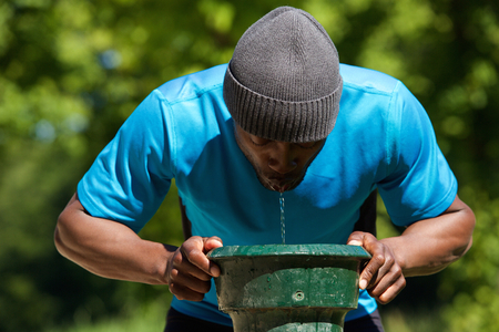 man drinking water: Thirsty african american man drinking water at the public park Stock Photo