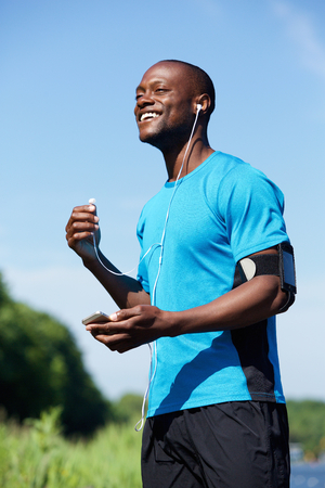 cool man: Portrait of an african american male runner smiling with headphones and mobile phone