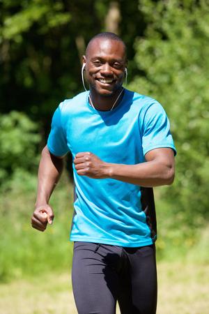 hombres corriendo: Retrato de un hombre afroamericano sonriente feliz correr en el exterior Foto de archivo