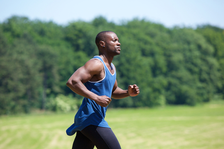MEN: Side view portrait of a fit exercising man running outside