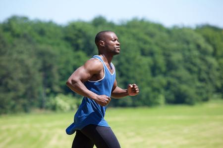 corriendo: Vista lateral retrato de un hombre ejercer ajuste se ejecuta fuera