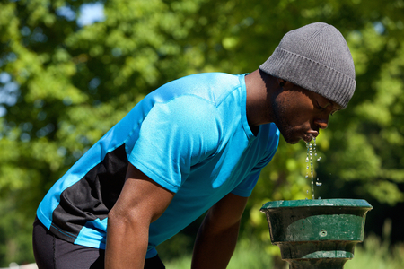 fountain: Side portrait of a young black man drinking water from a water fountain in public park Stock Photo