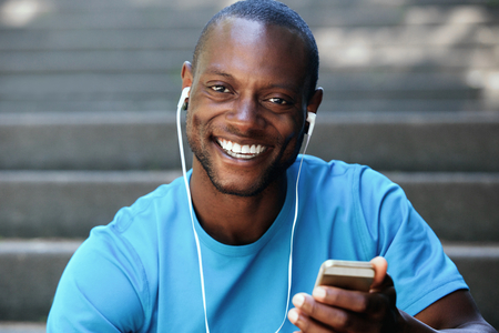 black people: Smiling african american guy holding mobile phone listening to music on headphones
