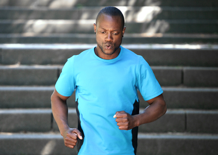 run down: African american man running down stairs keeping fit