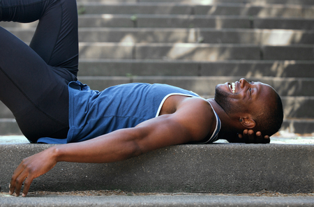 man lying down: Smiling young man lying down on back outside Stock Photo