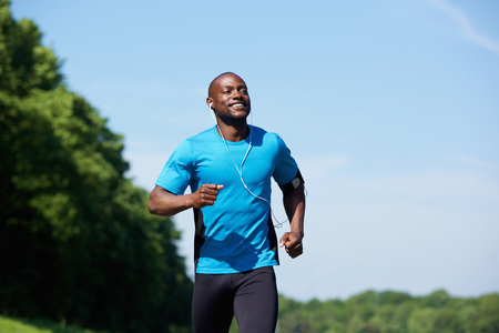 run: Portrait of an active african american man running exercise workout outdoors