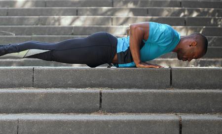 ropa deportiva: Retrato lateral de un hombre afroamericano en forma haciendo flexiones