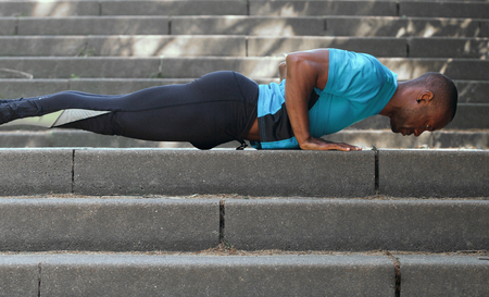 young man portrait: Side portrait of a fit african american man doing push ups Stock Photo
