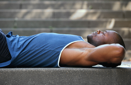 black male: One black man lying on back resting outside Stock Photo