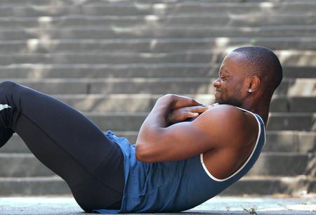 Side portrait african american man sport training workout sit ups outside