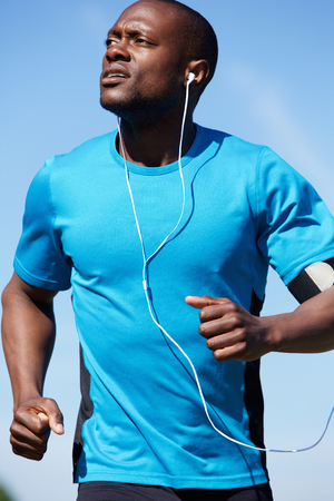outdoor fitness: Portrait of a healthy young man running outdoors