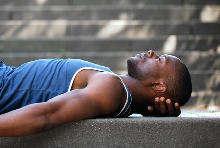 profile views: Side portrait of an african american man sleeping outside