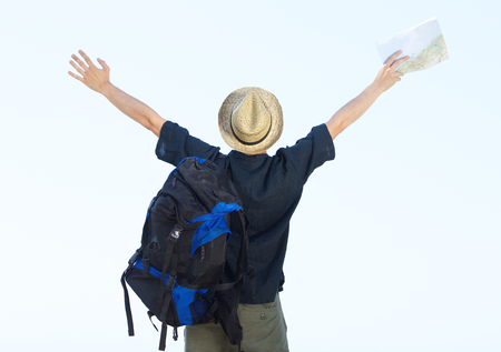 arm outstretched: Backpacker standing with arms spread open holding map Stock Photo