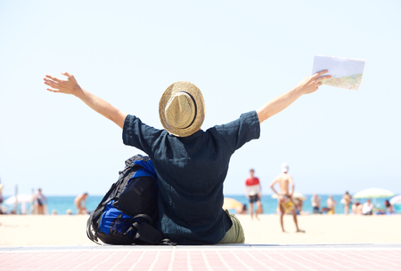 travel man sitting by beach with arms outstretched - from behind