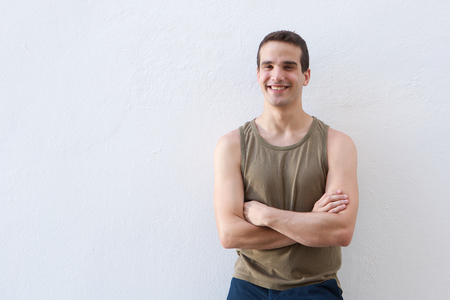 guy standing: Portrait of a smiling guy standing against white with arms crossed