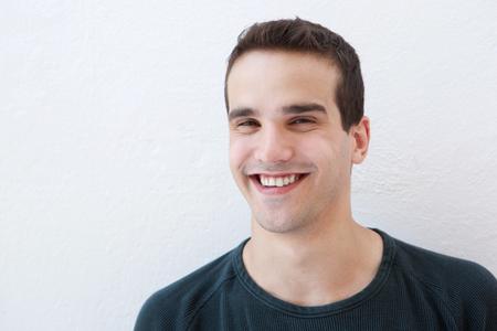 caras felices: Cerca de retrato de un hombre latino joven y sonriente contra el fondo blanco
