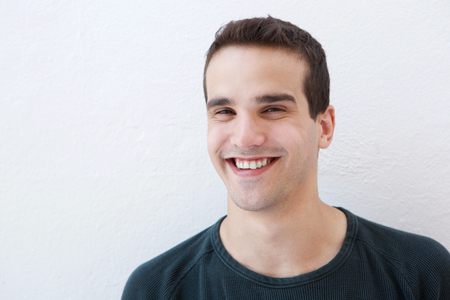 casual fashion: Close up portrait of a young latin man smiling against white background