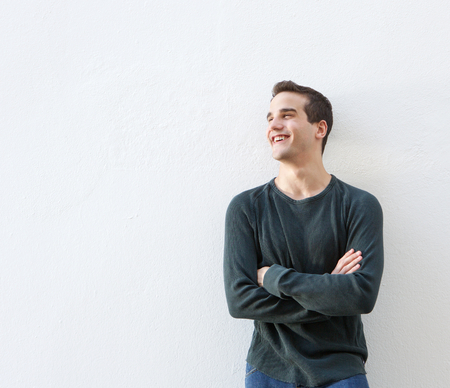 one person: Portrait of a young man standing against white background with arms crossed Stock Photo