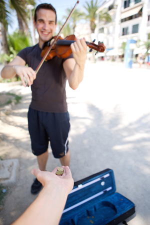 busker: Smiling male busker playing violin outside for money Stock Photo