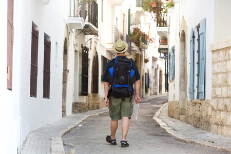 lost city: Man walking with backpack and map lost in town - from behind Stock Photo