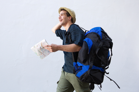 personas mirando: Portrait of a cheerful traveling man walking with bag and map