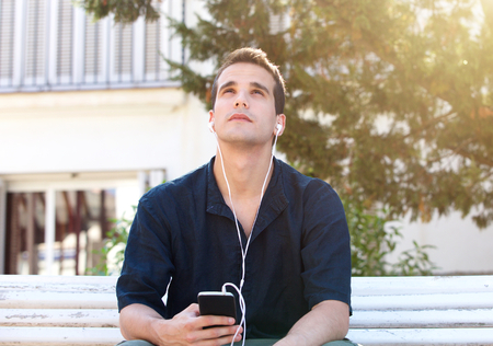 white men: Portrait of a man with mobile phone and earphones looking up Stock Photo