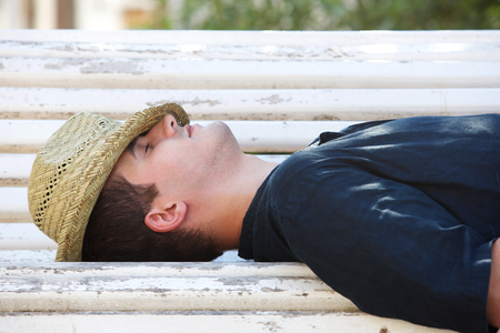 shut down: Side portrait of a man sleeping on park bench outside